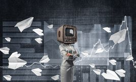 Business woman with old TV instead of head. Business woman in suit with old TV instead of head keeping arms crossed while standing against flying paper planes Royalty Free Stock Photo