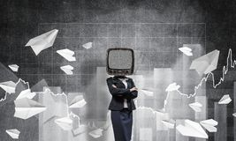 Business woman with old TV instead of head. Business woman in suit with old TV instead of head keeping arms crossed while standing against flying paper planes Royalty Free Stock Images