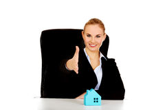 Business woman with an open hand ready for handshake and blue paper house on the desk Stock Image
