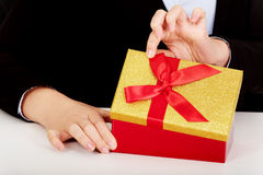 Business woman opens a gift box behind the desk Royalty Free Stock Photos