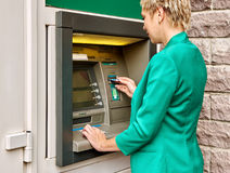 Business woman operates ATM Royalty Free Stock Photo