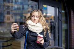 Business woman outdoor with coffee and mobilephone do selfie. Young and pretty woman using phone holding a cup of coffee in the dark cafe Royalty Free Stock Photography
