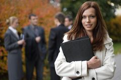 Business woman in an outdoor environment. With colleagues on the background at autumn time royalty free stock photo