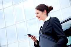 Business woman outside with mobile phone, smiling Royalty Free Stock Photos