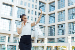 Business woman outside on the phone and shows  hand hello Royalty Free Stock Photo