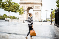 Business woman in Paris. Lifestyle portrait of a young stylish business woman walking outdoors near the famous triumphal arch in Paris Royalty Free Stock Photography