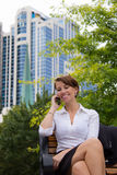 Business woman on park bench talks on phone Stock Images