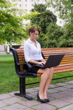 Business woman on park bench working with laptop computer Royalty Free Stock Images