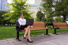Business woman on park bench working with laptop computer Stock Photos
