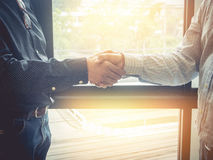 Business woman and partner shaking hands in office. vintage filt. Er effect Royalty Free Stock Photo