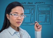 Business woman with pen and website mock up against blue background Stock Photos