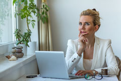 Business woman pensively sits with a laptop in home office. Royalty Free Stock Image