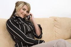 Business woman on the phone. Beautiful woman sitting on the sofa in living room wearing businesss wear and talking on the phone Stock Image