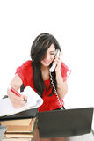Business woman on phone. Smiling young business woman on phone taking notes in office Royalty Free Stock Photography