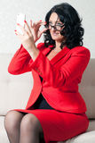 Business woman and phone. Adult business woman in red formal suit and mobile phone Stock Photography