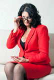 Business woman and phone. Adult business woman in red formal suit and mobile phone Royalty Free Stock Image