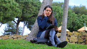 Business woman on the phone getting angry in park. Gorgeous woman sitting in park working with phone and tablet stock video