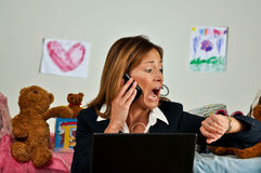 Business woman on phone looks at watch and is late royalty free stock photography