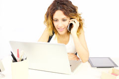 Business woman on the phone in office happy looking pc. Gorgeous lady at work in office Stock Photos