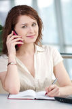 Business woman on phone taking notes Royalty Free Stock Photography
