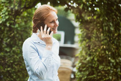 Business Woman on the Phone. A young businesswoman in a blue shirt talking on the phone in a garden - at home or at an office Stock Photos