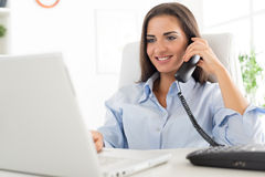 Business Woman Phoning In Office. Young business woman phoning in office, sitting at an office desk in front of laptop, in which looks with a smile on her face Royalty Free Stock Images