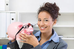Business woman with piggy bank. Smiling business woman with savings in piggy bank, at workplace Stock Photography