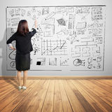 Business woman point at business concept chart on wall. Background Royalty Free Stock Photography