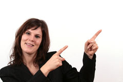 Business Woman Pointing. A young business woman is smiling while pointing towards something Royalty Free Stock Photo