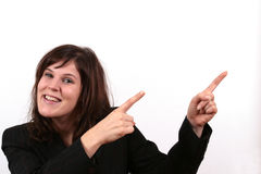 Business Woman Pointing. A young business woman is smiling while pointing towards something Royalty Free Stock Images