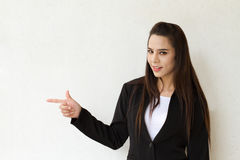 Business woman pointing at blank space. Female business executive pointing at blank space Stock Photography