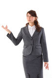 Business woman pointing at copyspace. A young beautiful business woman pointing at copyspace Stock Image