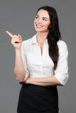 Business woman pointing at copyspace. A beautiful young business woman pointing and looking at copyspace, over grey background Royalty Free Stock Photo