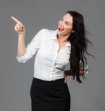 Business woman pointing at copyspace. A cheerful beautiful business woman pointing and looking at copyspace, over grey background Royalty Free Stock Image