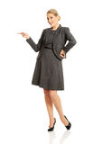 Business woman pointing at copyspace on the left.  Royalty Free Stock Photos