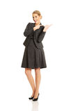 Business woman pointing at copyspace on the right.  Stock Images