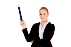 Business woman pointing for copyspace or something with huge pen.  Stock Image