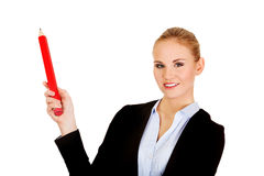 Business woman pointing for copyspace or something with huge pen.  Stock Images