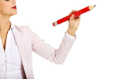 Business woman pointing for copyspace or something with huge pen.  Stock Photos