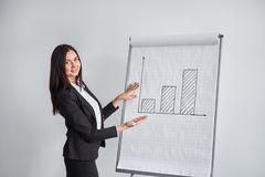 Business woman with graph in office, pointing at the diagram. Business woman is pointing at the diagram Royalty Free Stock Photos