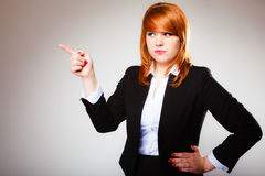 Business woman pointing with finger. Advertisement concept - redhead business woman pointing with finger showing blank copy space on gray background Royalty Free Stock Image
