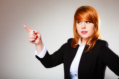 Business woman pointing with finger. Advertisement concept - redhead business woman pointing with finger showing blank copy space on gray background Royalty Free Stock Photos