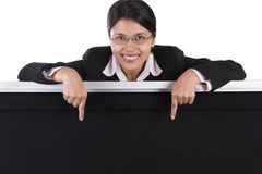 Business woman pointing to the blackboard. Blackboard to post message or announcement, if you need more room to place text or else just enlarge the area and copy Stock Photo