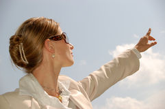Business Woman Pointing to the Distance. Pretty young woman in front of blue sky pointing to the distance Royalty Free Stock Image
