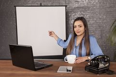 Business woman pointing to an empty blackboard behind her back royalty free stock photo