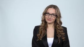 Business woman points finger away over grey background with copy space, slow motion. Smiling businesswoman talking and points finger away over grey background stock footage