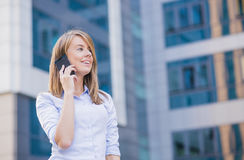 Business woman portrait outdoors talking at the phone with modern building as background. Royalty Free Stock Photography
