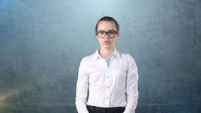Business woman portrait in white skirt on isolated background looking stright with hair ban,orange and black glasses. Royalty Free Stock Image