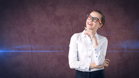 Business woman portrait in white skirt on isolated background. Model looking up with hair ban, orange and black glasses. stock image