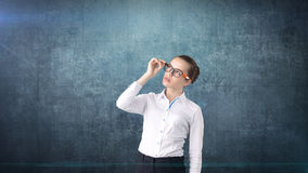 Business woman portrait in white skirt on isolated background. Model looking up with hair ban, orange and black glasses. Royalty Free Stock Images